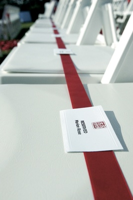 Long red ribbon on ceremony chairs labeled reserved seats