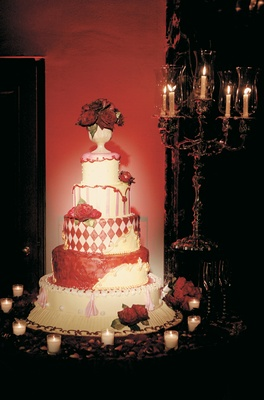 Five layer red pink and white cake with rose topper