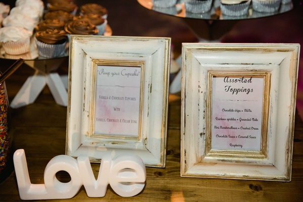 Wedding dessert table cupcake stand with framed signs featuring additional toppings and cupcake