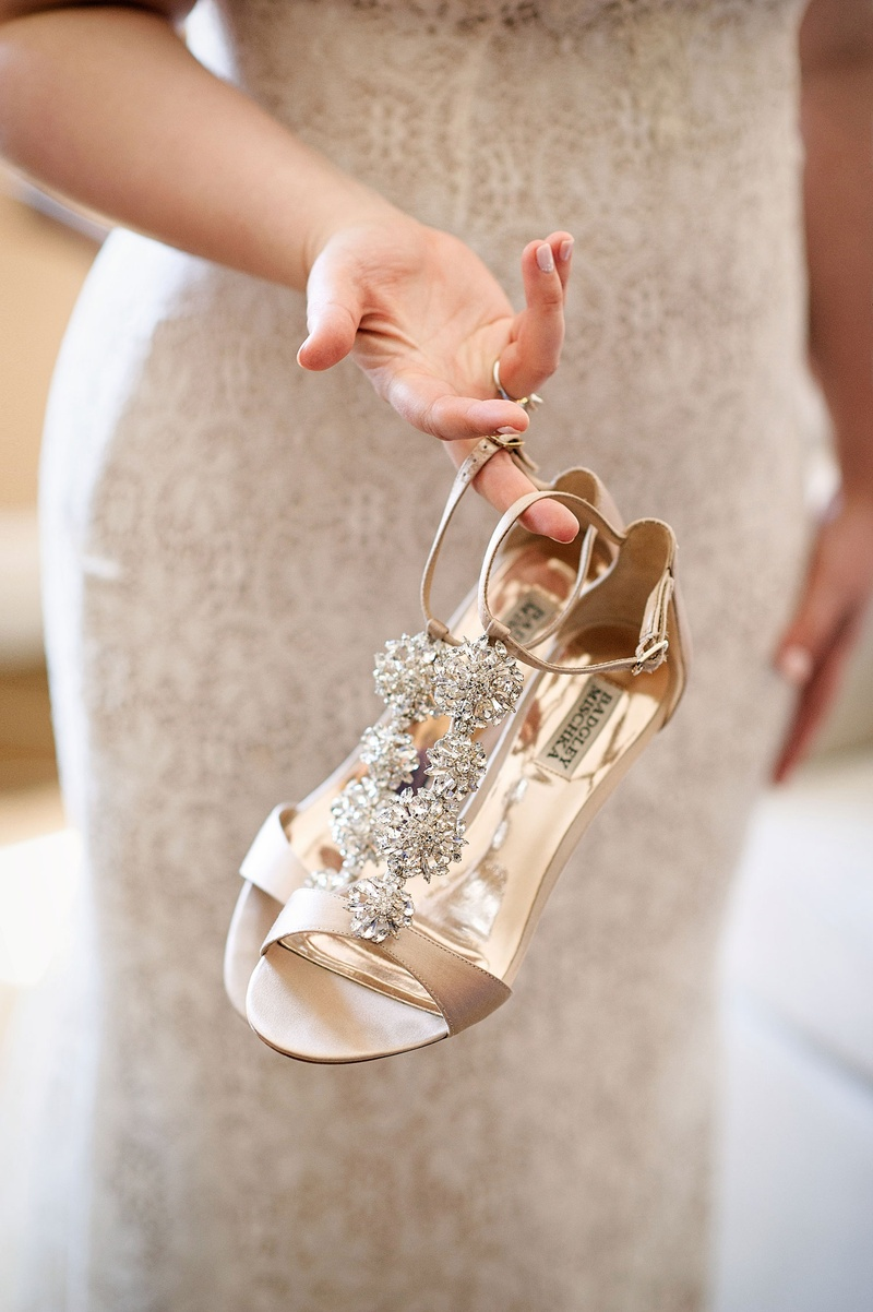 Bride holding Badgley Mischka shoes with nude and crystal details ankle strap open toe