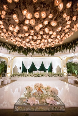 wedding reception white dance floor with sweetheart table crystal and flower decor live band stage