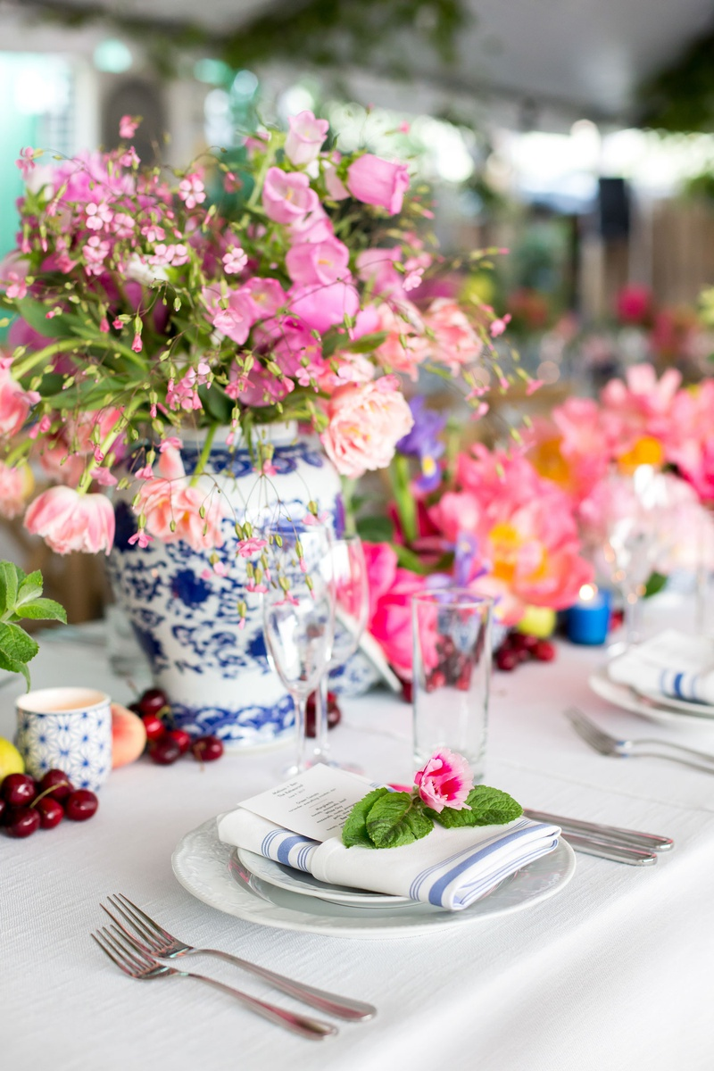 chinoiserie vases, pink flowers, blue and silver striped napkins topped with pink flower and leaves