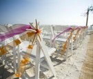 White chairs on sand decorated with starfish