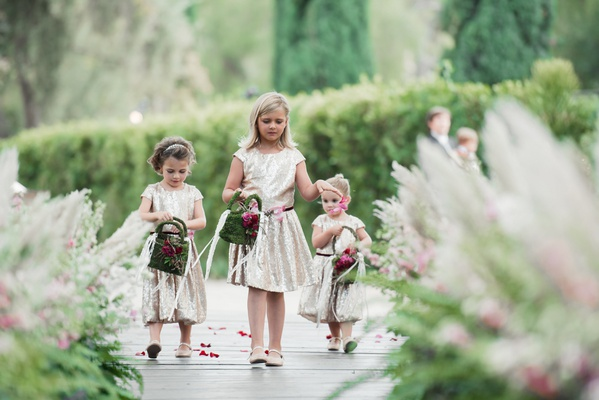 Flower girls in gold dresses and moss purses with pink flowers outside