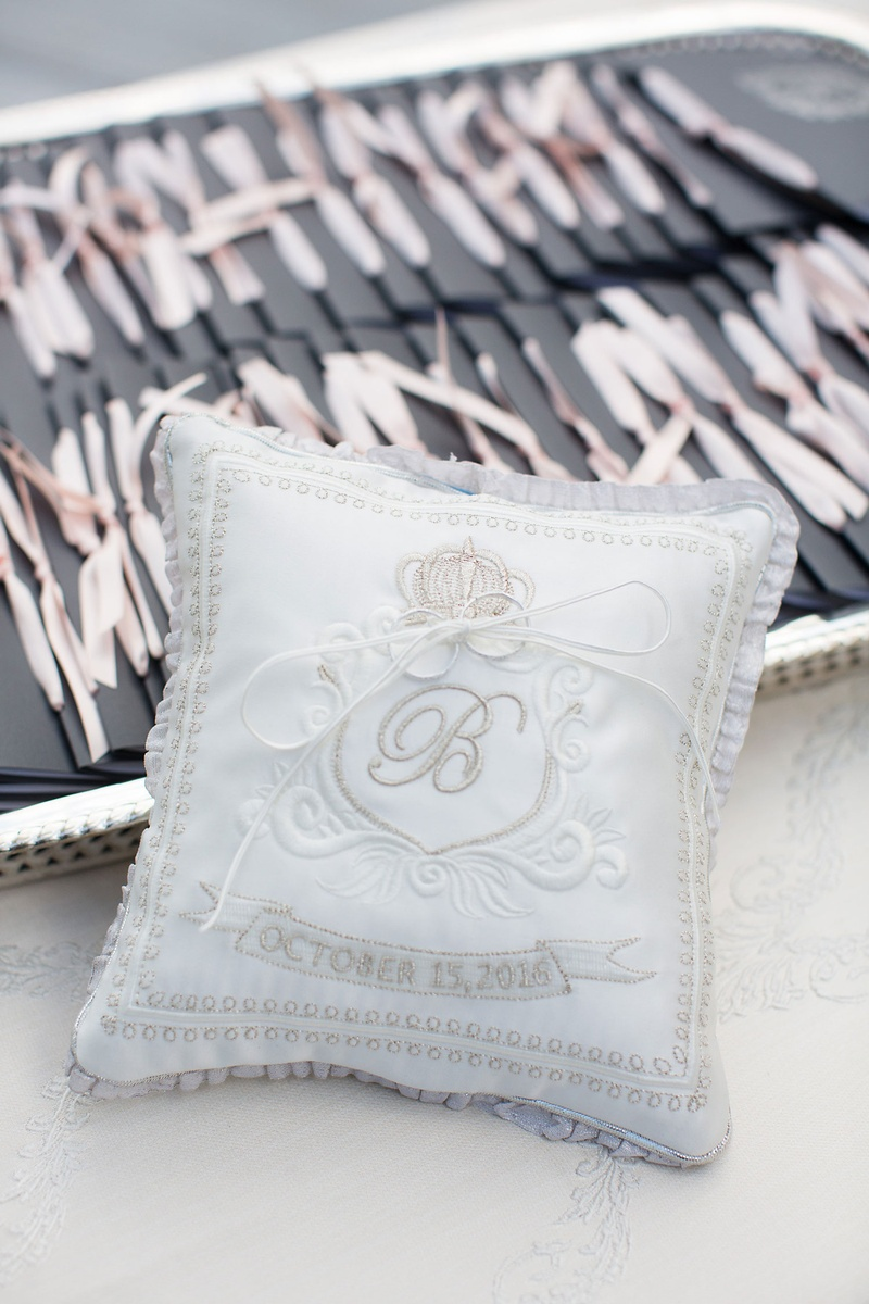 Wedding rings attached to ring pillow with ribbon grey silver satin monogram and wedding date