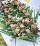 Garden wedding reception cocktail hour with tray of pork, asparagus appetizers
