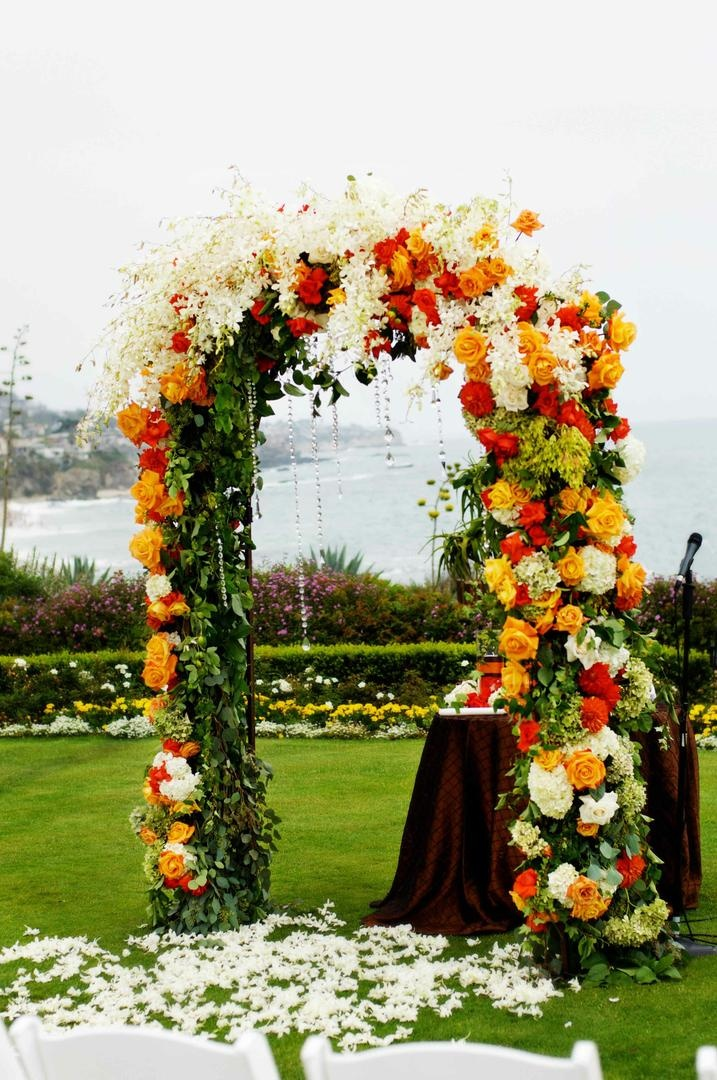 Ceremony arch covered in vibrant flowers and crystals