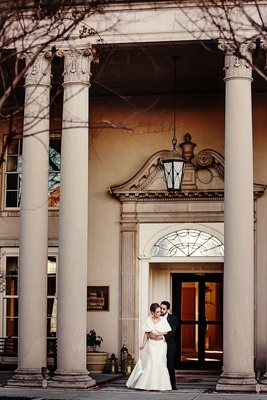 Bride and groom in front of marble columns of The Biltmore Ballrooms