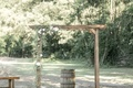 Wedding ceremony arch flowers on one side wood barrel in center alter raw wood details