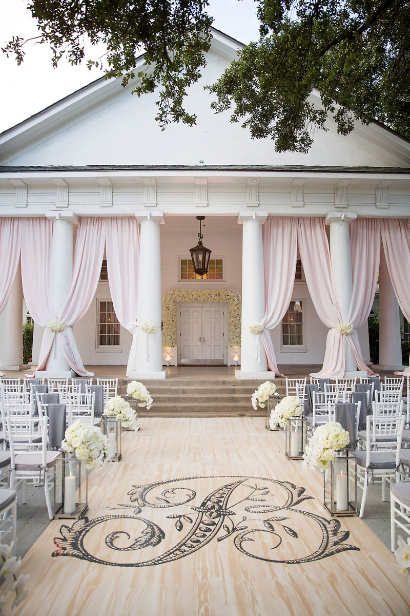 Wedding ceremony on porch with wood aisle runner pink drapery between columns white flowers chairs