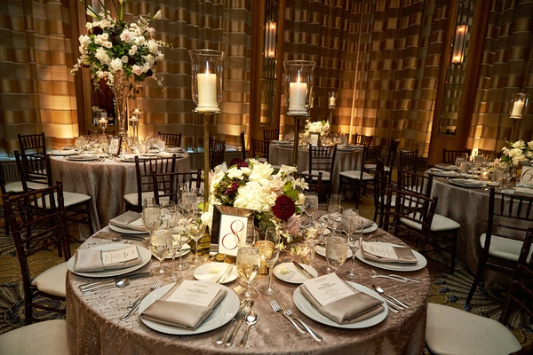 small round wedding table with silver tablecloth pillar candle low high centerpiece
