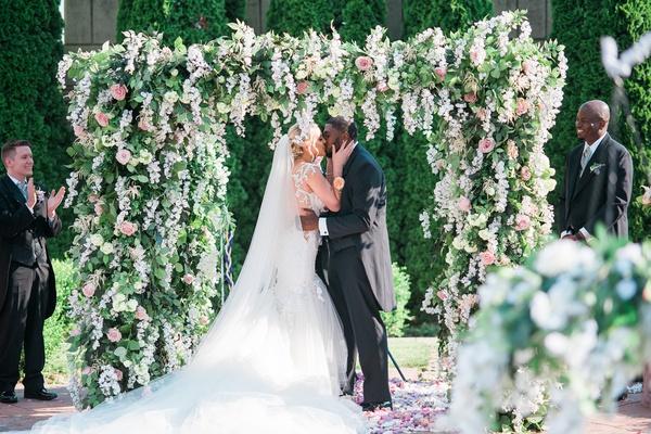 bride in galia lahav bridal gown kissing groom under lush ceremony arbor, donathan hurley survivor