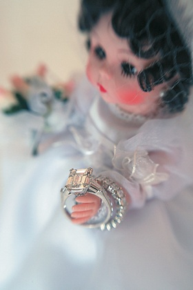 Porcelain doll with wedding dress holding wedding rings
