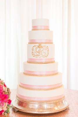 wedding cake white fondant pink ribbon gold jewels and gold monogram crest