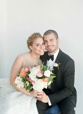 Bride in sparkle dress and groom in tuxedo with bouquet