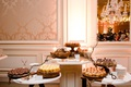wedding reception ballroom cake stands with different desserts and cupcakes branches decor damask