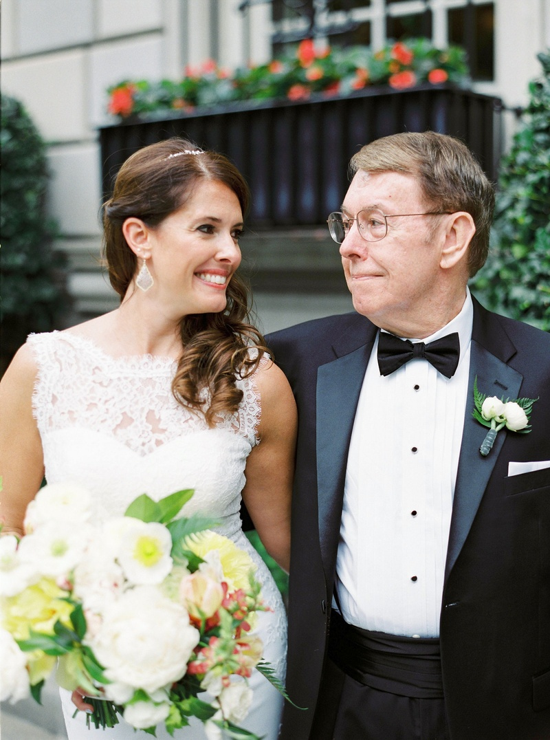 Bride in white lace wedding dress and bouquet smiles at father of bride in tuxedo with bow tie