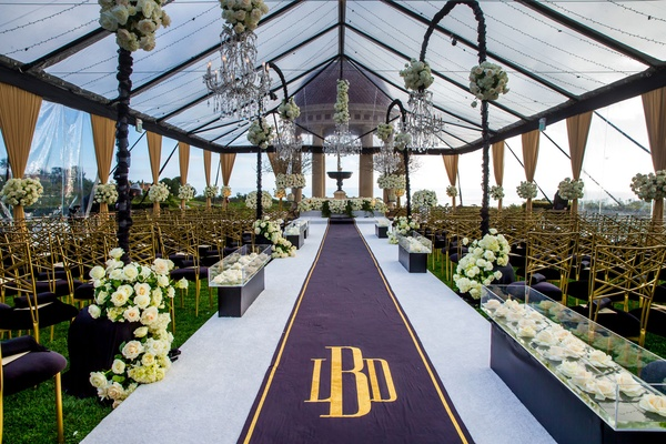Wedding ceremony resort at pelican hill tent clear with flower chandeliers black gold aisle runner