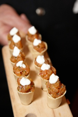 Wedding reception appetizers of tomato salad in bread cups topped with cream on wood tray