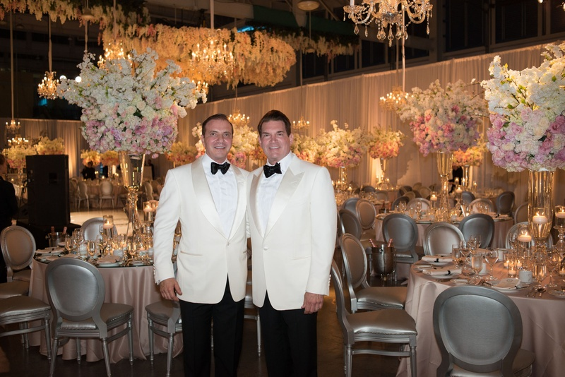 Couple In White Tuxedos In Reception