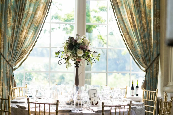 Wedding table in front of window with vintage curtains