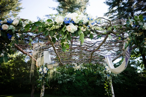top of chuppah formed of woven branches and white flowers