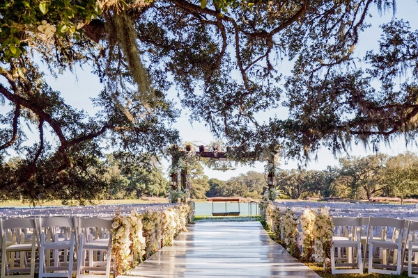 white ceremony under oak tree near lake in texas