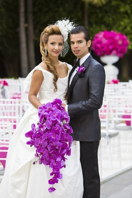 Bride in net blusher veil with cascading orchid bouquet and groom