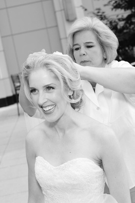 Black and white photo of bride getting hair done