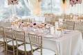 Wedding reception rectangle table linen gold chair gold glassware low centerpiece long mirror detail