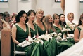 Bridesmaids in v-neck dresses with white gloves