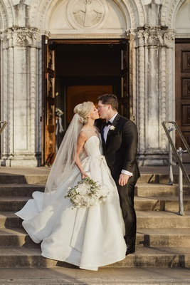 bride in illusion neck wedding dress isabelle armstrong kiss groom tuxedo church ceremony dallas tx