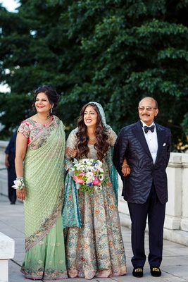 pakistani bride in colorful sleeved gown being walked down the aisle by her mother and father