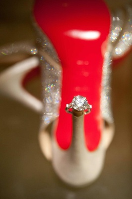 Round diamond engagement ring on heel of Christian Louboutin red sole