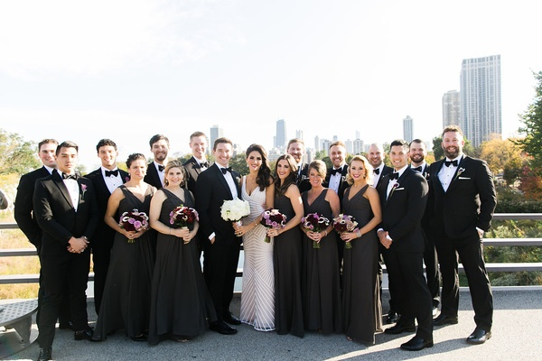 Bride and groom on balcony in Chicago with bridesmaids in charcoal dresses and groomsmen in tuxedos