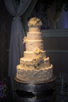 six layer wedding cake with icing rosettes, monogram, dot details, fresh flowers