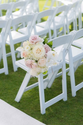 White ceremony chair on grass lawn with white and pink rose, orchid, hydrangea flower arrangement