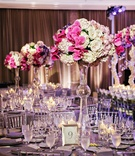 Tall Latour trumpet vase with white hydrangea, lavender rose, and fuchsia orchid centerpiece