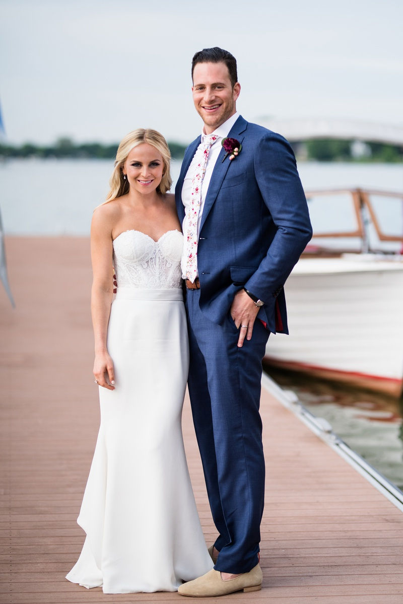 bride in strapless lihi hod bridal gown with groom in blue suit & floral tie on dock of lake mendota