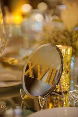 a glittered gold table number in roman numerals on a reflective surface mirror table number