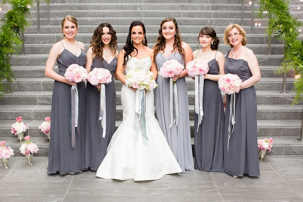 Bridesmaids in long grey and silver dresses with pink bouquets and silver silk ribbon
