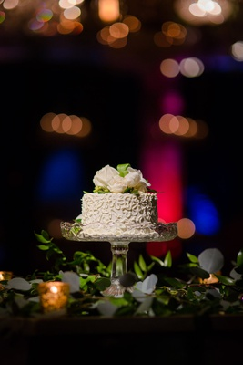 small wedding cake on glass cake stand fresh flowers on top cutting cake only