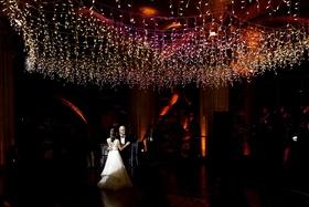 Wedding reception father daughter dance on dance floor dark with twinkle lights overhead