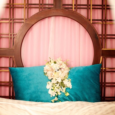 white floral bridal bouquet and teal pillow pink curtains cream cushion
