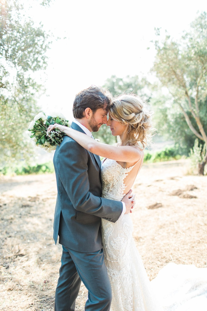 Bride closes eyes and puts arms around groom while holding bouquet berta wedding dress grey suit