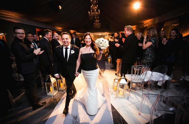 groom in black tuxedo and bride in black and white gown walk back up aisle after vows