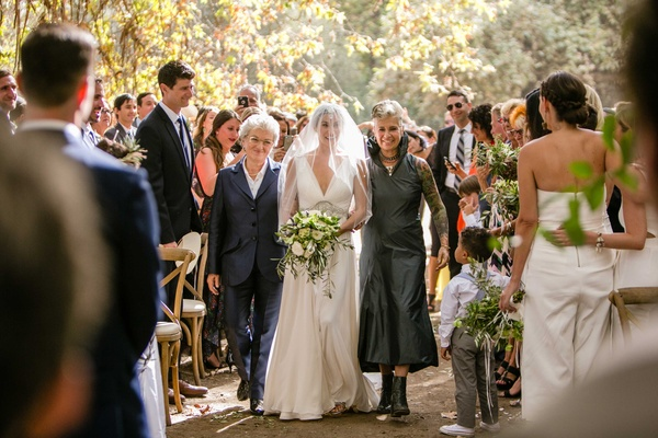 Bride in v neck wedding dress walks down aisle with two mothers same-sex couple