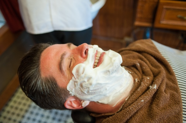 Groom with shaving cream on face at barbershop