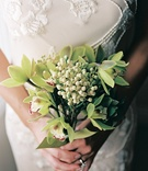 Bride in beaded gown holds green flower bouquet