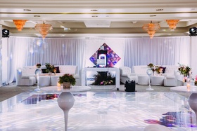 DJ booth and lounge furniture at dancing after party spot reception white purple chandeliers